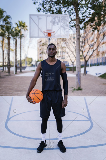 Young man holding basketball on basketball court