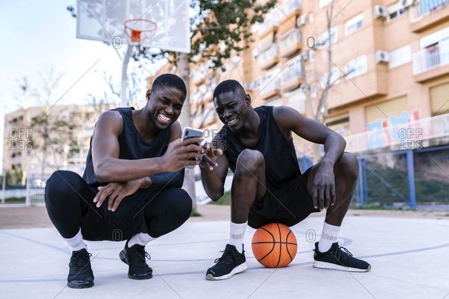 Basketball players using smartphone on basketball court