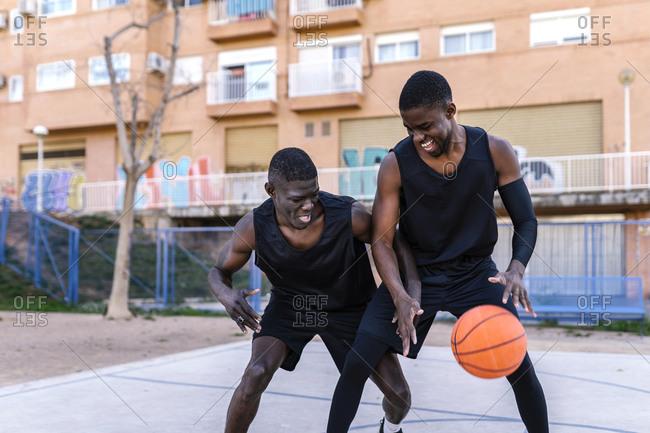 Basketball players playing basketball on court outdoors