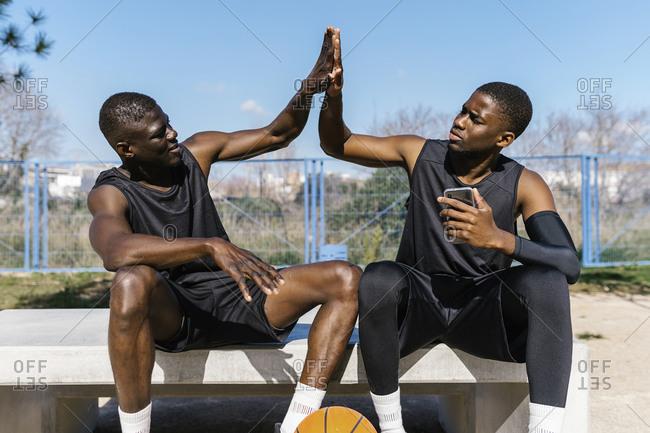Basketball players high-fiving on outdoor basketball court