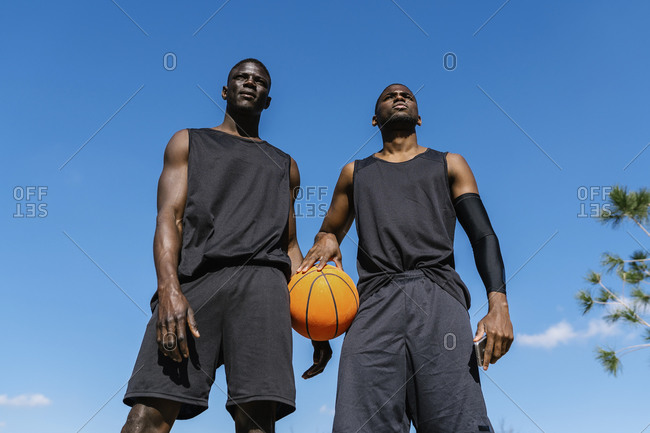 Young men holding basketball on basketball court