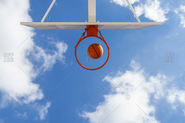 Basketball and hoop- blue sky- upward view