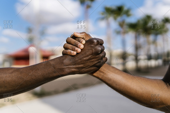 Young men shaking hands on outdoor basketball court