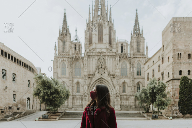 Woman wearing face mask looking away while standing against Barcelona Cathedral during quarantine- Barcelona- Spain