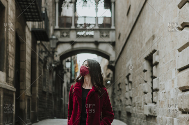 Woman wearing face mask looking away while standing on empty alley of Gothic Quarter during quarantine- Barcelona- Spain