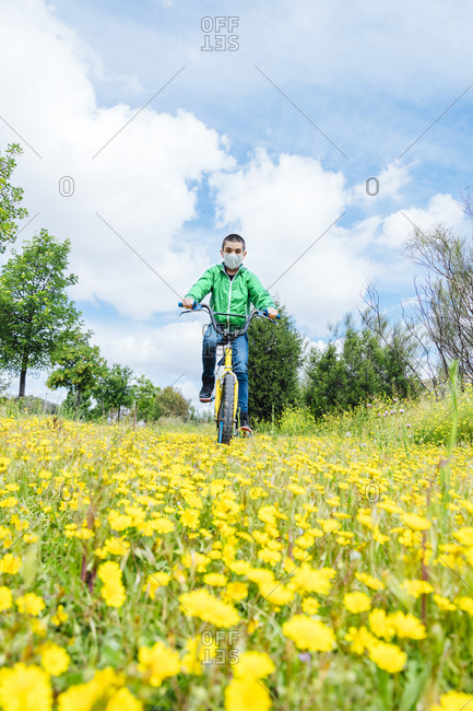 Full length of boy wearing face mask cycling over yellow flowers on field against sky