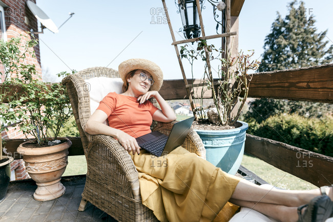 Portrait of pensive mature woman with laptop relaxing on terrace