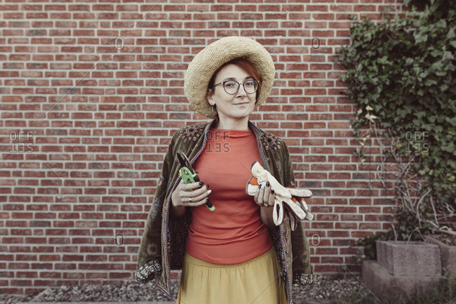 Portrait of mature woman with gardening gloves and pruner standing in front of brick wall