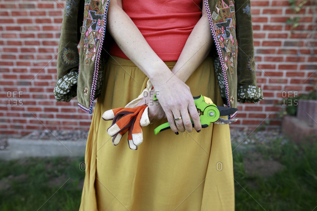Crop view of woman with gardening gloves and pruner