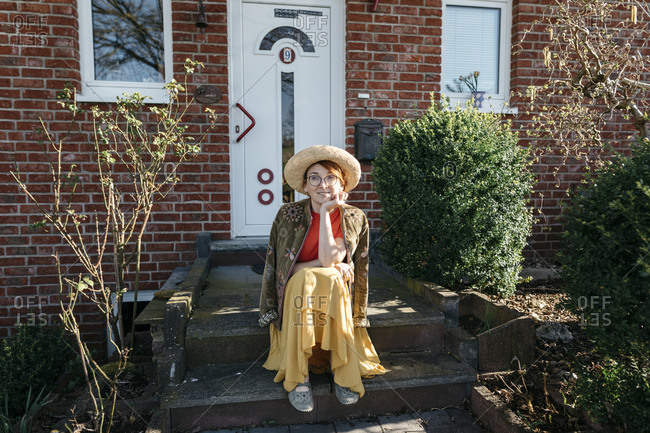 Portrait of smiling mature woman with straw hat sitting on stairs of one-family house