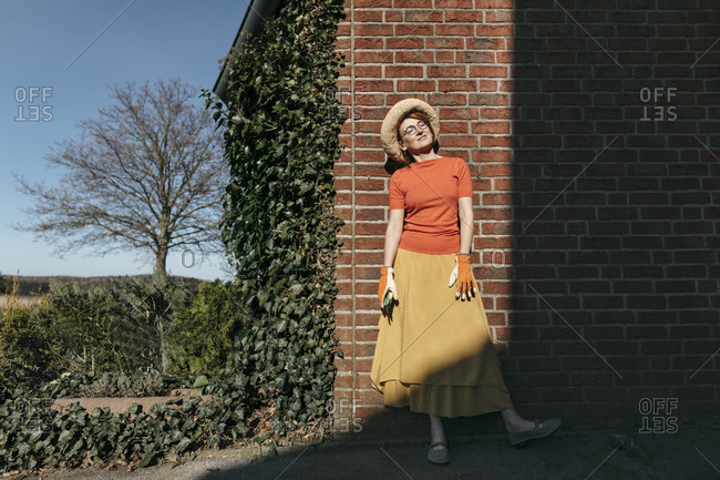 Portrait of mature woman with gardening gloves and pruner standing in front of brick wall enjoying sunlight