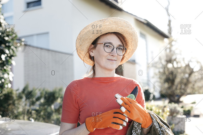 Portrait of mature woman with pruner wearing straw hat and gardening gloves