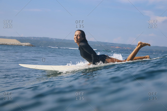 Happy woman lying on surfboard in the sea- Bali- Indonesia