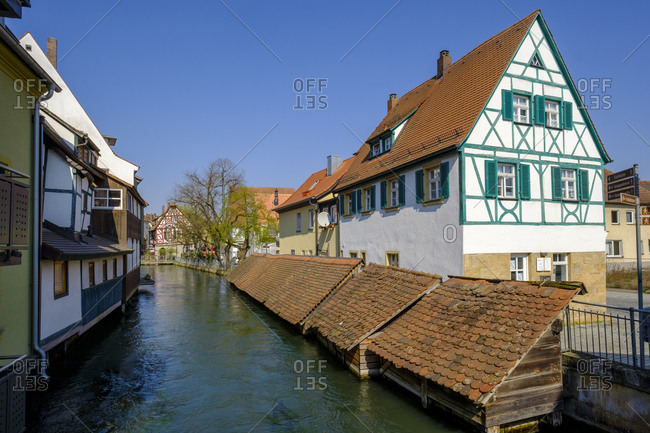 April 9, 2020: Germany- Bavaria- Forchheim- Half-timbered town house and fish boxes along Wiesent river canal