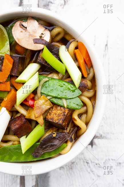 Bowl of Japanese miso soup with udon noodles- tofu- sugar snap peas- paprika- carrot- mu-err mushrooms- scallion and cilantro