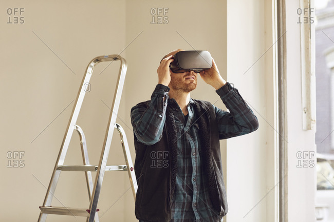 Man refurbishing shop location- using VR glasses