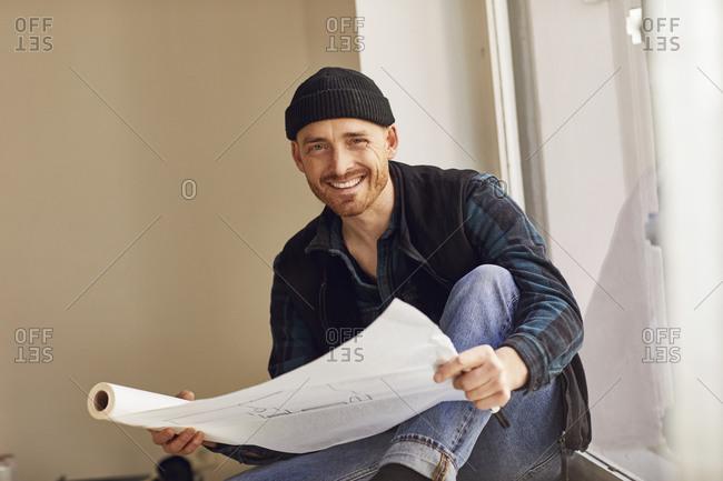 Man refurbishing shop location- sitting on windowsill- studying blueprint