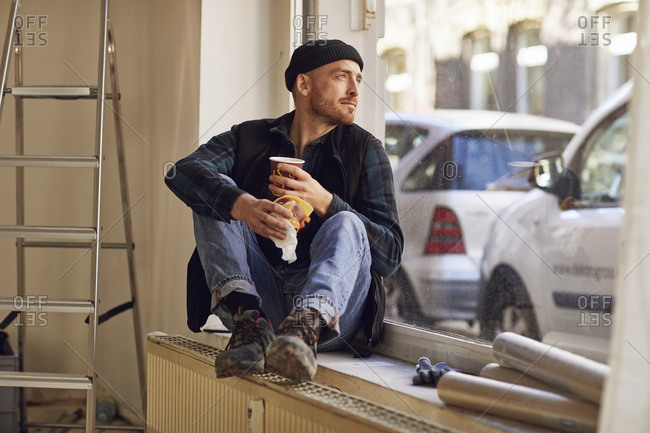 Man refurbishing shop location- sitting on windowsill- drinking coffee
