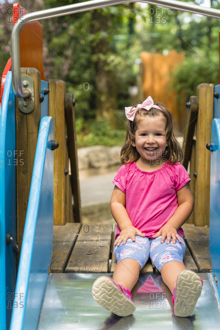Portrait of happy little girl sitting on playground slide