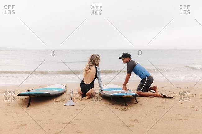 Instructor and woman kneeling while talking by paddleboards at beach