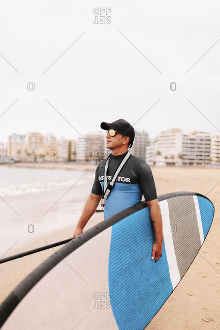 Instructor looking away while walking with paddleboard at beach against clear sky