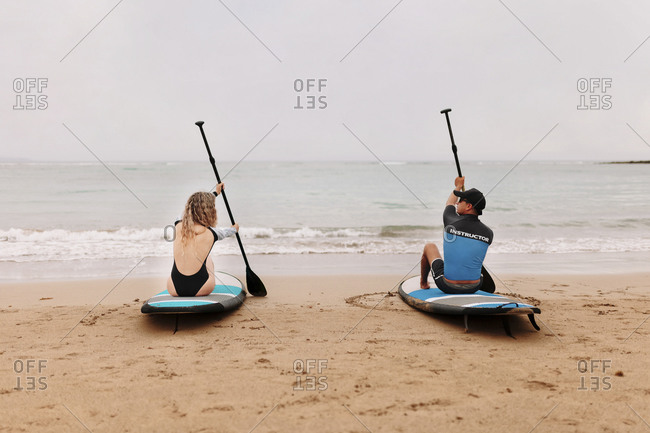 Rear view of instructor and young woman sitting on paddleboards with oars at beach