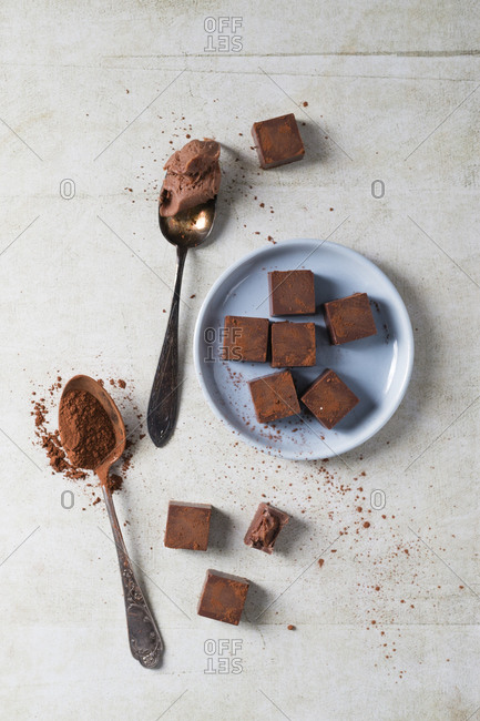 Two teaspoons and bunch of pralines with chocolate ganache