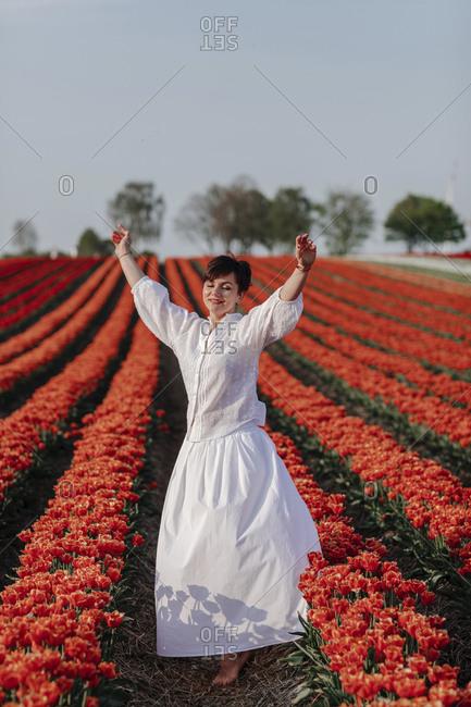 Portrait of smiling woman dancing in  tulip field