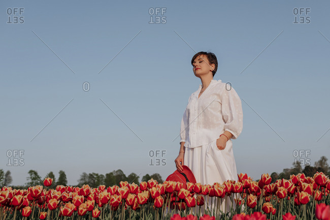 Portrait of woman with eyes closed  standing in tulip field