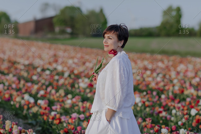 Portrait of smiling woman dressed in white standing in tulip field