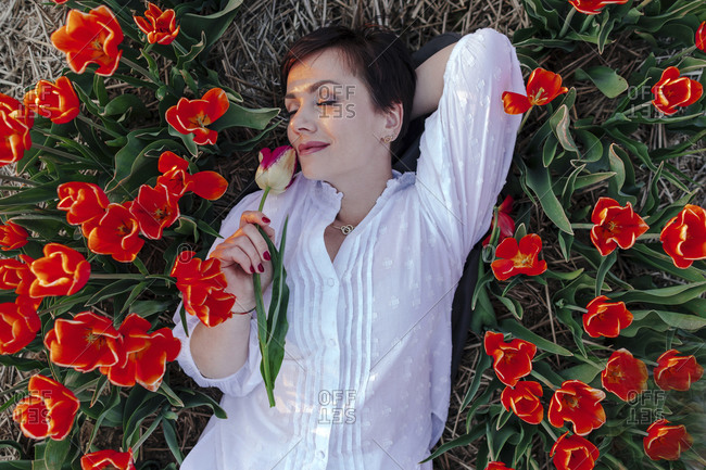 Portrait of smiling woman with eyes closed lying between tulips