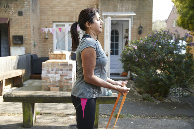 Side view of woman exercising with resistance band