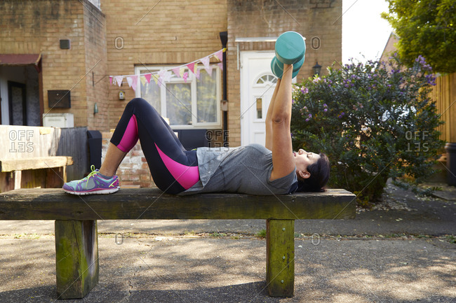 Full length side view of mature woman exercising with dumbbells on wooden bench at back yard