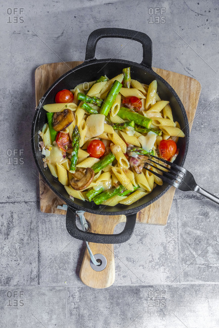 Pan of vegetarian pasta with asparagus- mushrooms- tomatoes and Parmesan cheese