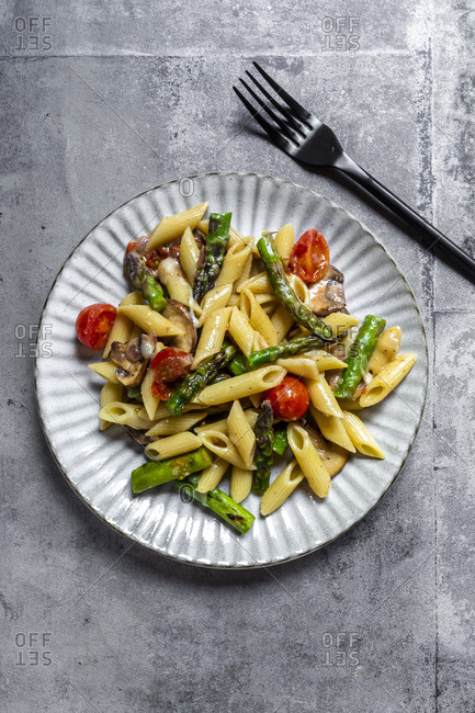 Plate of vegetarian pasta with asparagus- mushrooms- tomatoes and Parmesan cheese
