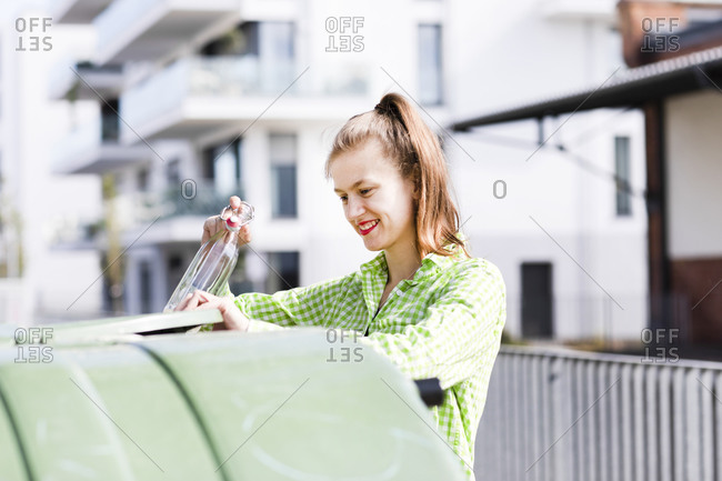 Smiling beautiful young woman throwing bottle in garbage can on sunny day