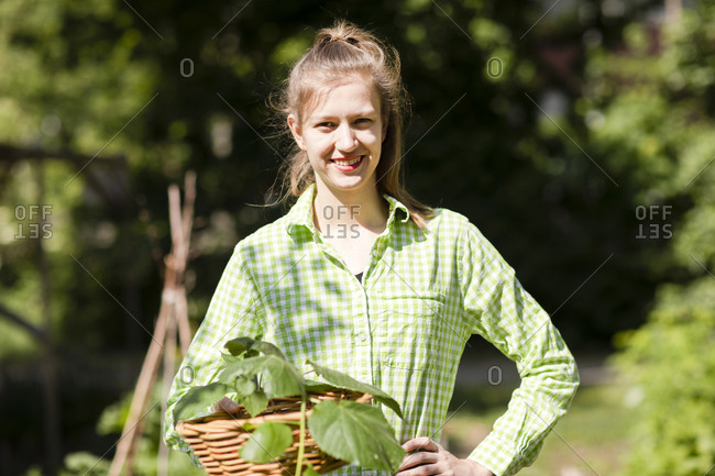 Portrait of smiling beautiful young woman holding wicker basket while standing at garden on sunny day