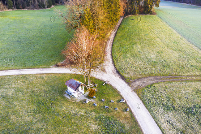 Germany- Bavaria- Egling- Drone view of St. Josefi Kapelle standing by countryside crossroad