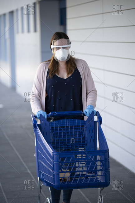 Woman walking while pushing shopping cart outside supermarket during COVID-19 pandemic