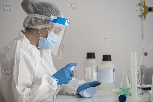 Woman in protective wear sitting at desk disinfecting cell phone