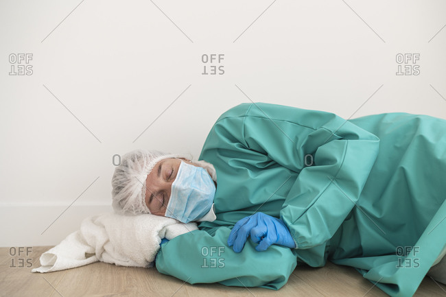 Exhausted woman wearing personal protective equipment lying on the floor