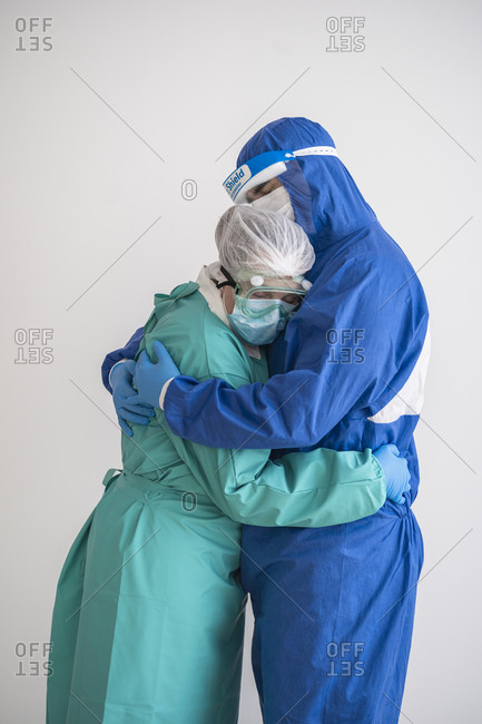 Couple in personal protective equipment embracing