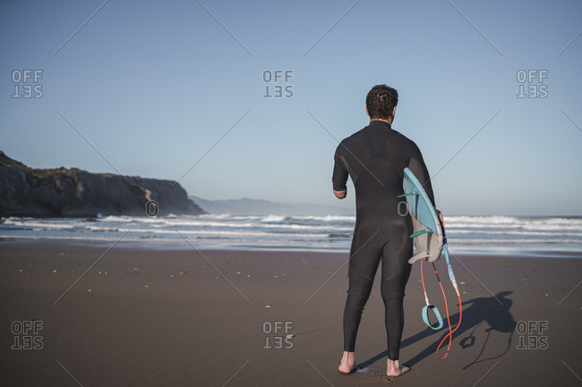 Rear view of handicapped surfer with surfboard at beach