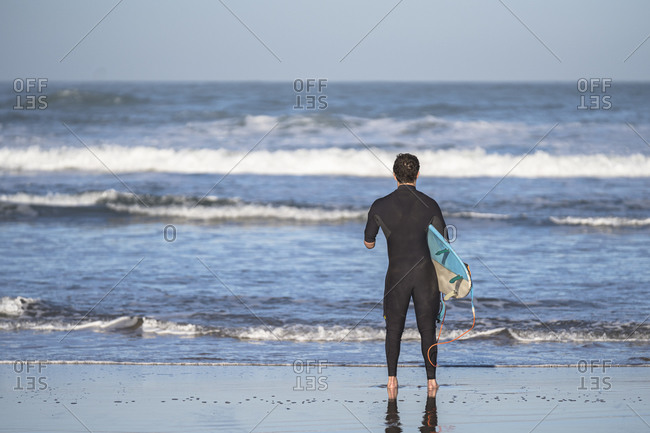 Handicapped surfer with surfboard at beach