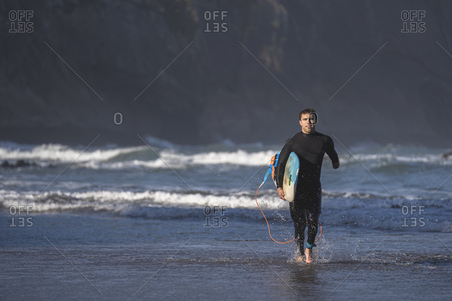 Handicapped surfer with surfboard running at beach