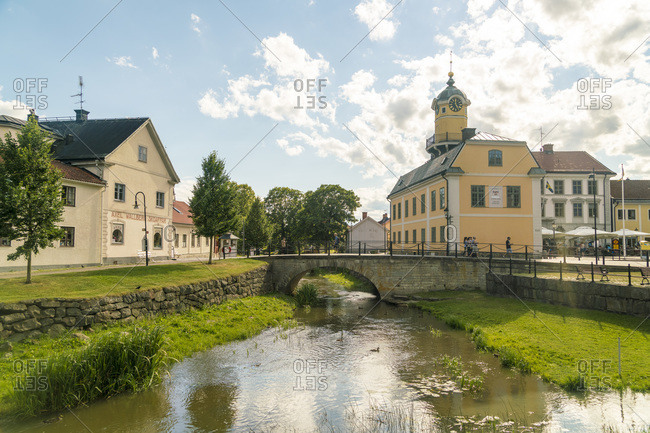 July 20, 2017: Sweden- Ostergotland- Soderkoping- Arch bridge over small city canal with town hall in background