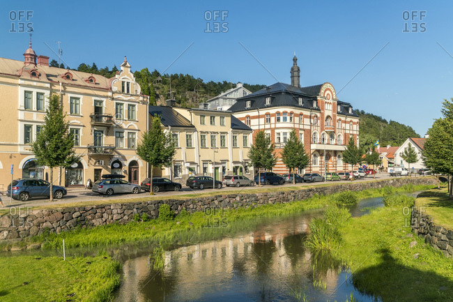 July 20, 2017: Sweden- Ostergotland- Soderkoping- Cars parked along row of houses standing along small river canal