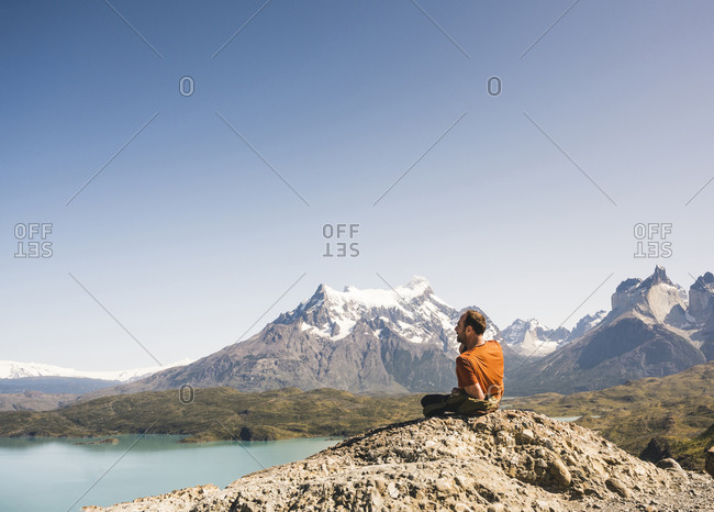 Hiker resting in mountainscape at Lago Pehoe in Torres del Paine National Park- Patagonia- Chile