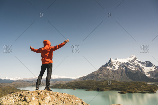 Hiker raising his arms in mountainscape at Lago Pehoe in Torres del Paine National Park- Patagonia- Chile