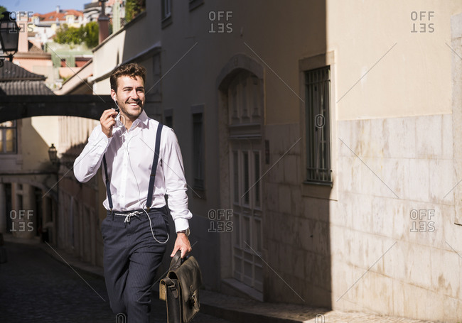 Smiling young man with earbuds in the old town- Lisbon- Portugal